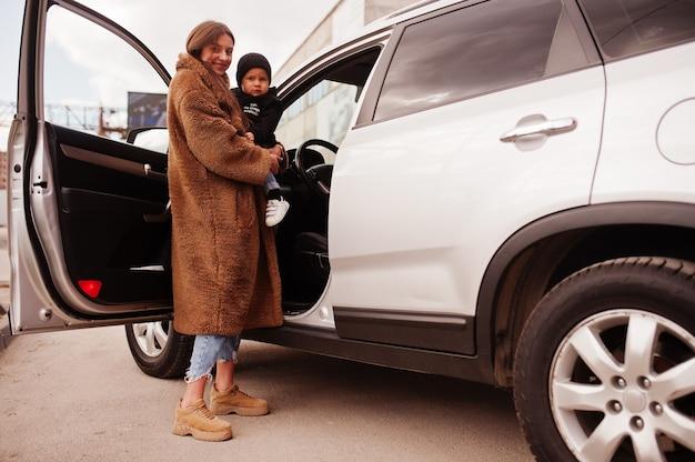 젊은 엄마와 아이가 suv 차 근처에 서 있습니다. 안전 운전 개념입니다.
