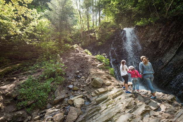 젊은 엄마와 아이들은 언덕의 암석과 폭포의 자연 광활한 광경을 바라보며 숲 속을 걸어갑니다.