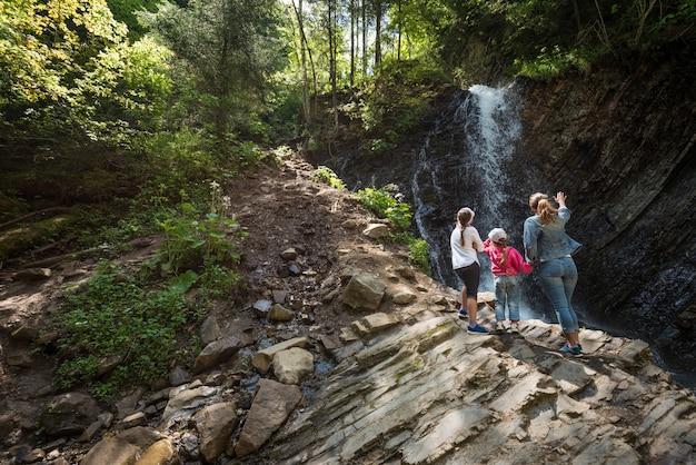젊은 엄마와 아이들은 언덕의 암석의 자연 광활한 광경을 바라보며 숲 속을 걸어갑니다.