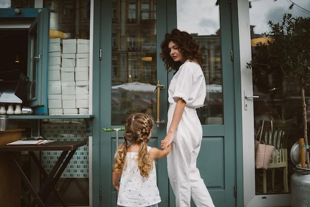 Молодая мать и милая маленькая дочь гуляют по улице