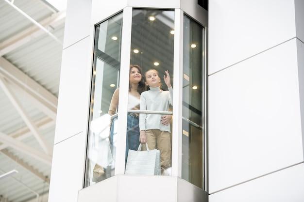 若い母と娘がショッピングモールで黒い金曜日のショッピング中にエレベーターで上向きに移動しながら何かを議論します。