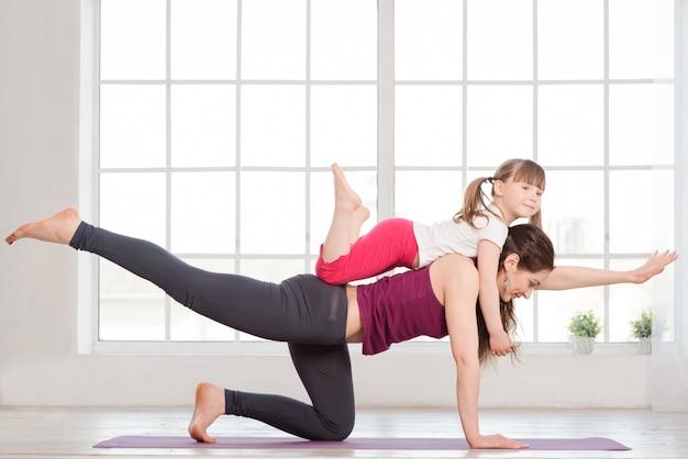 Молодая мать и дочь делают упражнения йоги