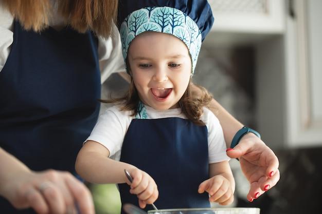 젊은 어머니와 부엌에서 딸 컵 케이크 반죽을 금형에 붓는다. 손을 클로즈업합니다.