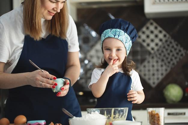 カップケーキを準備するキッチンで若い母と娘。女の子は生地を試します。