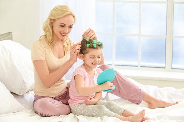 Молодая мать и дочь утром на кровати в помещении