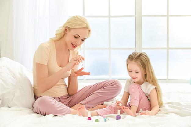 屋内のベッドで若い母と娘の朝