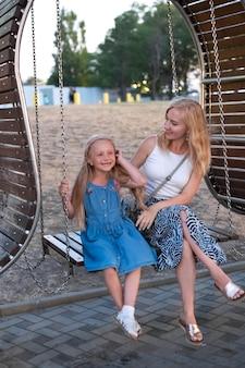 ブランコに乗っている若い母と娘。夏休み。子育てのコンセプト。