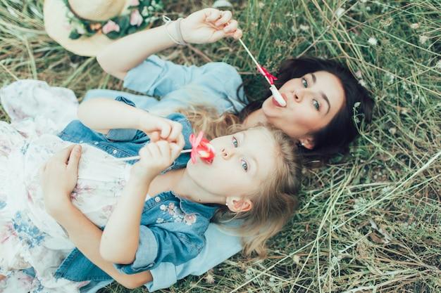 若い母親と娘の緑の芝生