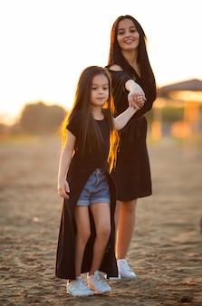 若い母と娘の演奏と砂浜の上を歩く