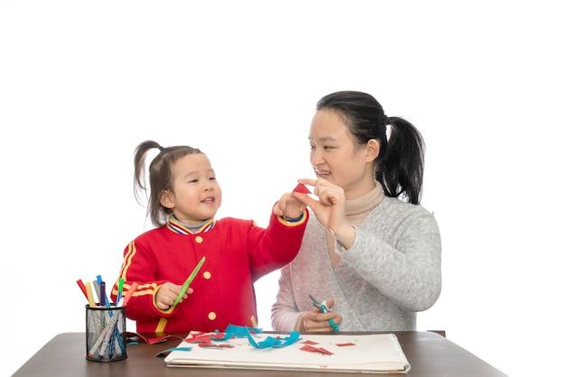 Молодая мать и дочь, играя вырезать из бумаги