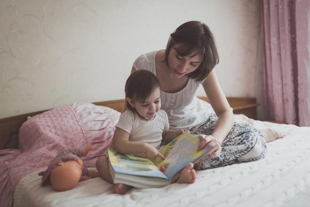 젊은 어머니와 딸 유아 독서 책 침대, 라이프 스타일에 앉아
