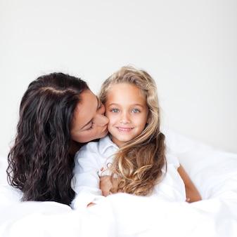 若い母親とdaugtherはベッドに抱かれている