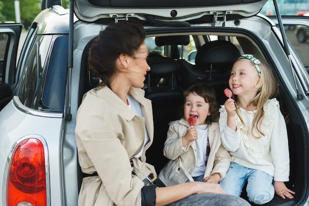 젊은 어머니와 그녀의 사랑스러운 dauthers 자동차 트렁크에 앉아.