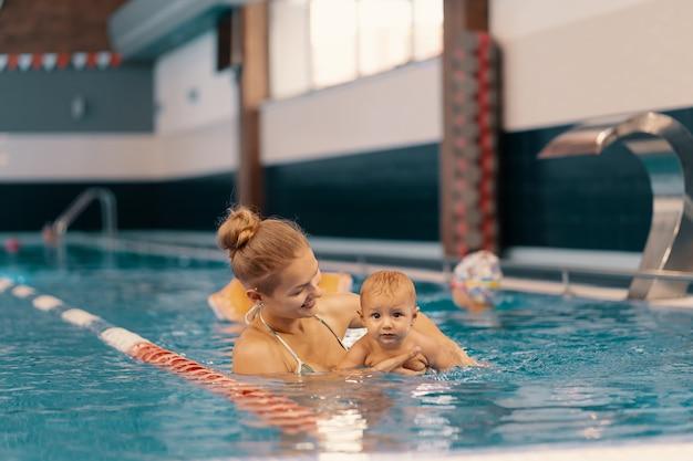 プールでベビースイミングのレッスンを楽しんでいる若い母親と彼女の赤ちゃん。お母さんと一緒に水で楽しんでいる子供 Premium写真