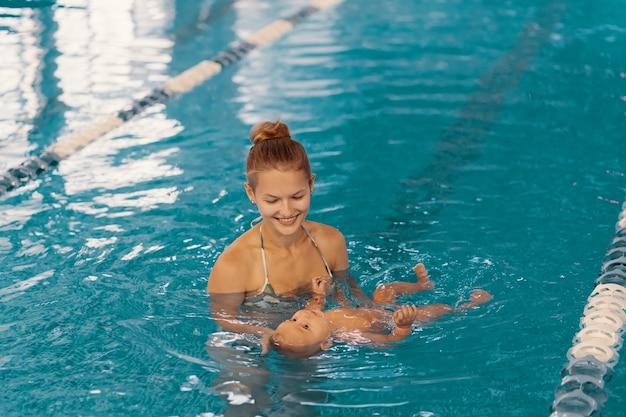 プールでベビースイミングのレッスンを楽しんでいる若い母親と彼女の赤ちゃん。お母さんと一緒に水で楽しんでいる子供