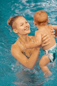 Молодая мать и ее ребенок, наслаждаясь уроком плавания ребенка в бассейне. ребенок веселится в воде с мамой