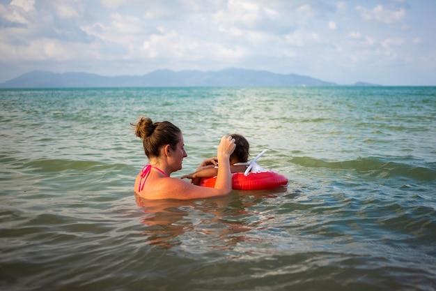젊은 엄마와 그녀의 아기 유아 바다에서 수영. 특별한 팽창식 구명 부표에 있는 아이.