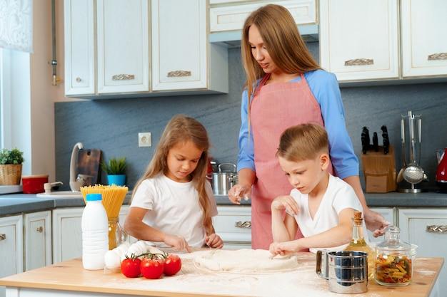 若い母親とかわいい子供たちが一緒にピザを調理