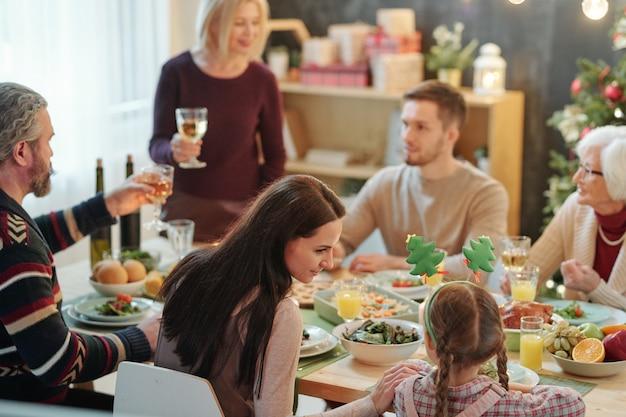 Молодая мать и ее милая маленькая дочь сидят рядом друг с другом за обслуживаемым столом во время семейного ужина в канун рождества