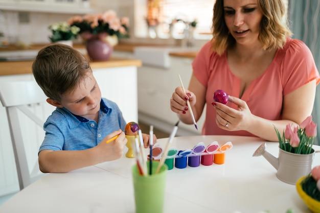 젊은 어머니와 그녀의 귀여운 아들이 부활절 달걀을 그리는 동안 즐겁게 놀고 있습니다