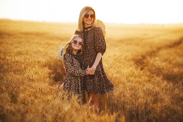 麦畑の晴れた日に麦畑で若い母と娘