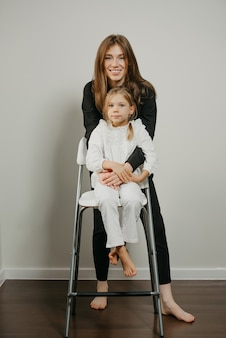 젊은 어머니와 키가 큰 의자에 그녀의 딸