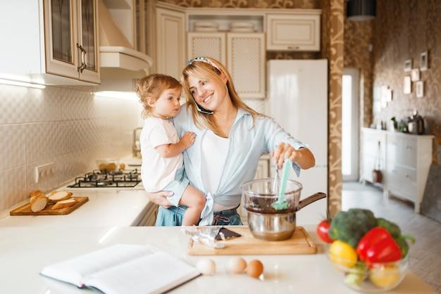 若い母親と彼女の娘は溶かしたチョコレートでペストリーを準備します。