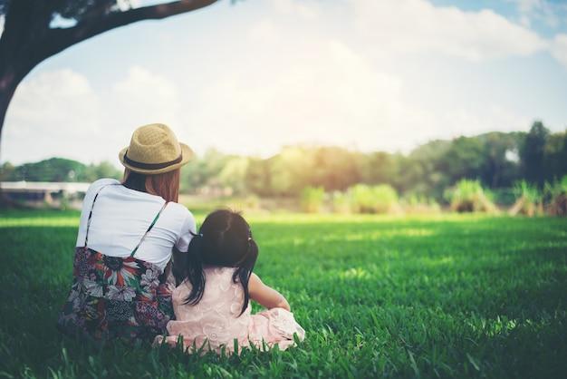 Молодая мать и ее дочь, расслабляющий, сидя на зеленой траве в парке