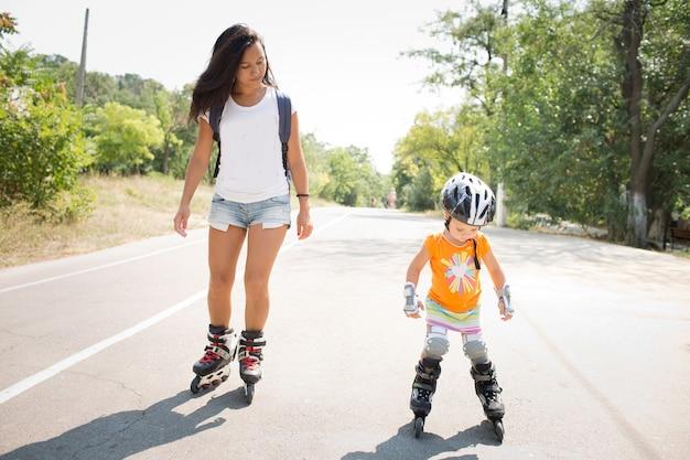 젊은 어머니와 그녀의 딸이 혼자 도로에서 롤러 스케이트를 타고 있습니다. 여름에 함께 즐겨요. 어머니는 딸에게 스케이트 타는 법을 가르칩니다. 하계