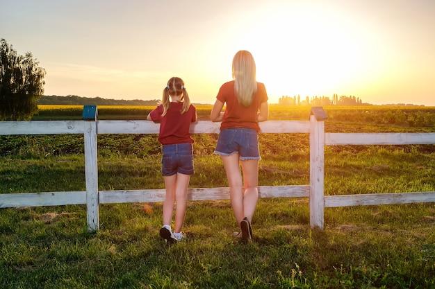 젊은 어머니와 그녀의 딸은 들판의 일몰 때 울타리 근처에 등을 대고 서 있다