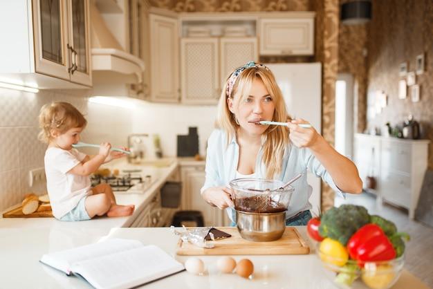 若い母親と娘は溶けたチョコレートを味わう。