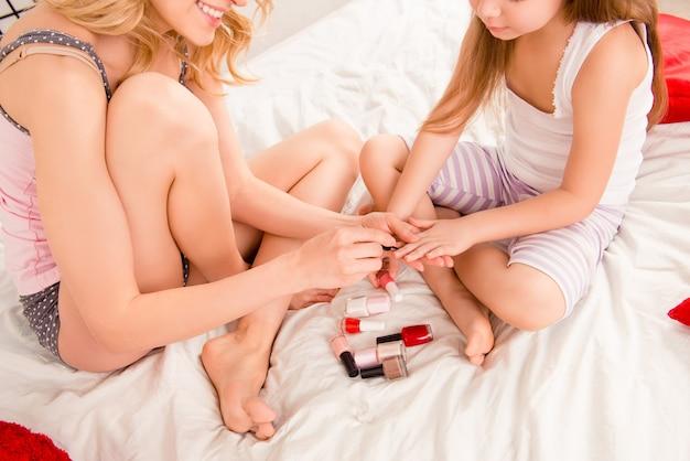 Молодая мать и ее дочь дочь красят ногти