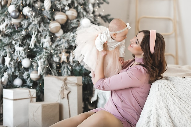 젊은 어머니와 그녀의 작은 아기 딸 크리스마스 트리