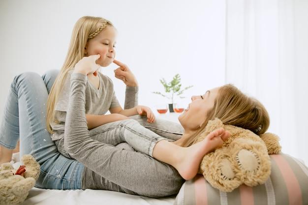 Молодая мать и ее маленькая дочь дома в солнечное утро. мягкие пастельные тона. счастливое семейное время на выходных. концепция дня матери. понятия семьи, любви, образа жизни, материнства и нежных моментов.