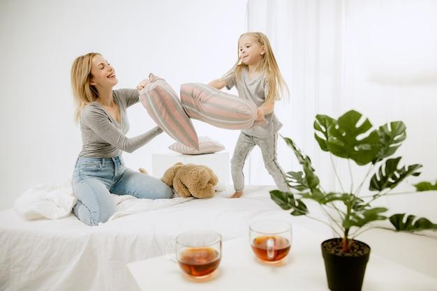晴れた朝、家にいる若い母親と幼い娘。やわらかなパステルカラー。週末の幸せな家族の時間。母の日のコンセプト。家族、愛、ライフスタイル、母性、優しい瞬間の概念。