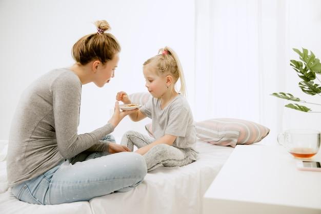 젊은 어머니와 화창한 아침에 집에서 그녀의 작은 딸. 부드러운 파스텔 색상. 주말에 행복한 가족 시간. 어머니의 날 개념. 가족, 사랑, 라이프 스타일, 모성 및 부드러운 순간 개념.