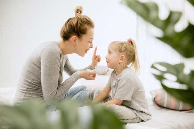 Молодая мать и ее маленькая дочь дома в солнечное утро. мягкие пастельные тона. счастливое семейное время на выходных. концепция дня матери