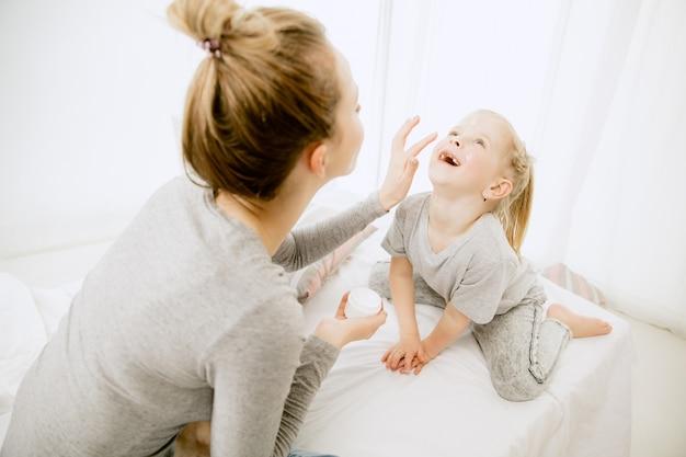 晴れた朝、家にいる若い母親と幼い娘。やわらかなパステルカラー。週末の幸せな家族の時間。母の日のコンセプト