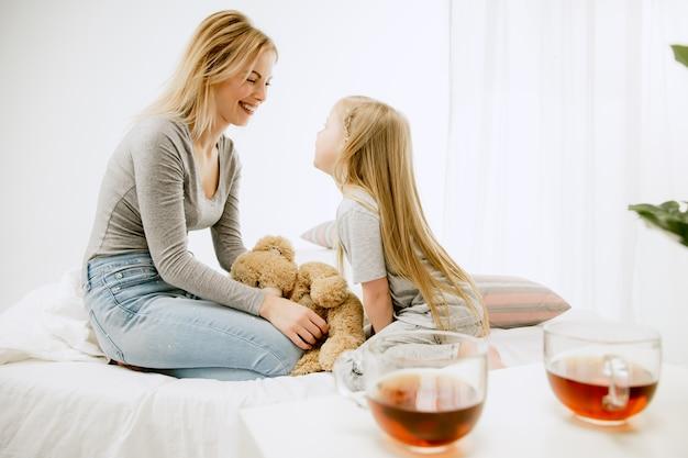 晴れた朝、家にいる若い母親と幼い娘。やわらかなパステルカラー。週末の幸せな家族の時間。
