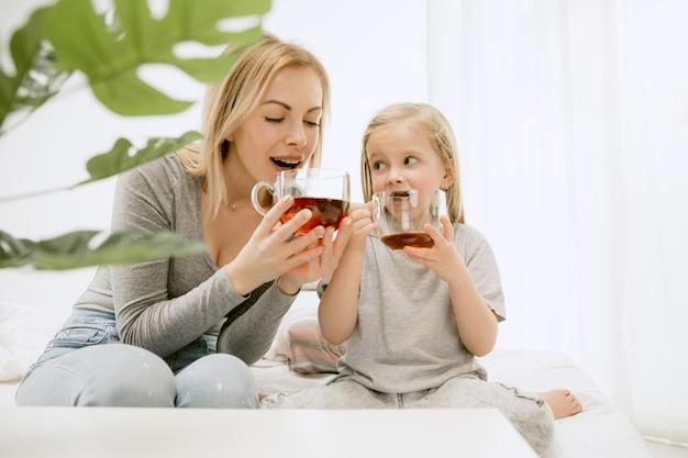 Молодая мать и ее маленькая дочь дома в солнечное утро. мягкие пастельные тона. счастливое семейное время на выходных.