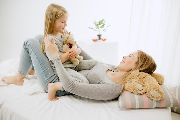 晴れた朝に家にいる若い母親と彼女の小さな娘