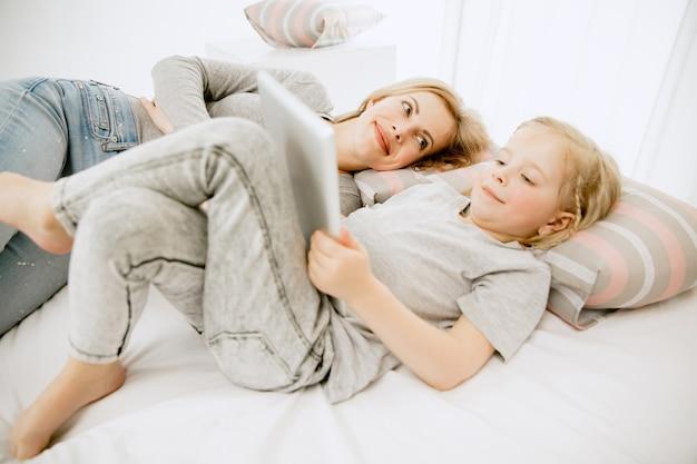 젊은 어머니와 화창한 아침에 집에서 그녀의 작은 딸.