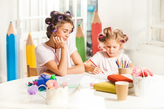 若い母親と彼女の小さな娘が家で鉛筆で描く