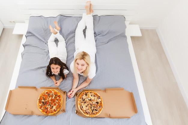若い母親と彼女の小さな娘はピザを食べて楽しんでいます