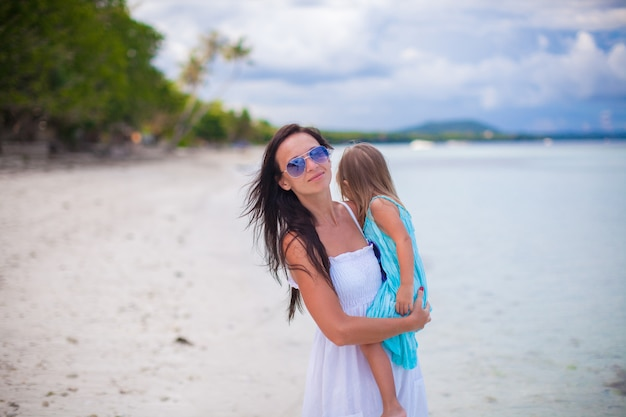 Молодая мать и ее маленькая дочь, наслаждаясь пляжным отдыхом