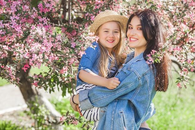 Молодая мать и ее маленькая дочь весело вместе на открытом воздухе