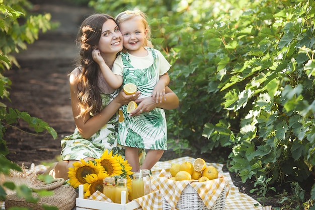 若い母親と彼女の小さな娘は屋外で楽しんでいます。かなりの家族。