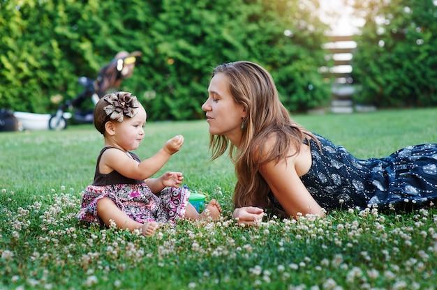 若い母親と彼女の小さな娘が芝生で遊んで