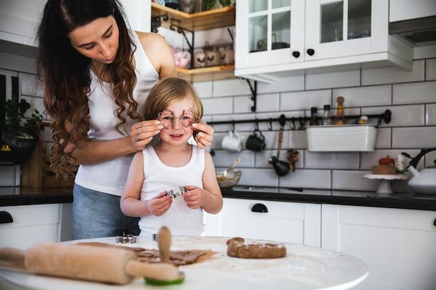 若い母親と幼い息子が家庭の台所で一緒にクッキーを焼く
