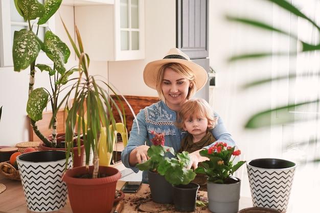 젊은 어머니와 그녀의 아들은 집에서 집 꽃 재배에 종사하고 있습니다.